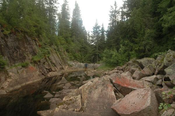 Den gamle fløtningsdammen ligger i enden av en smal kløft.