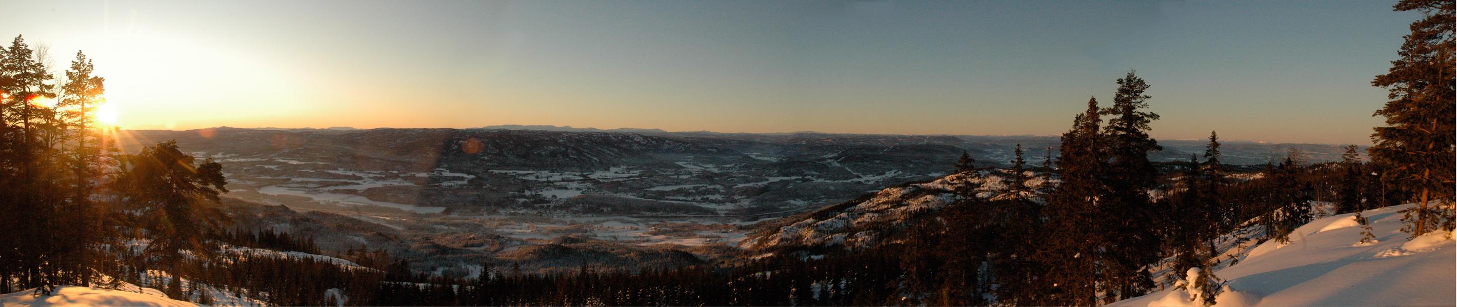 Fra Snaukollen ser du bygdene langs Drammenselva øverst i Eiker og syd i Modum.  I horisonten rekker av snødekte fjell som lyser rosa i solnedgangen.
